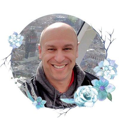 Photo of Yaniv Feldman smiling in a frame with flowers